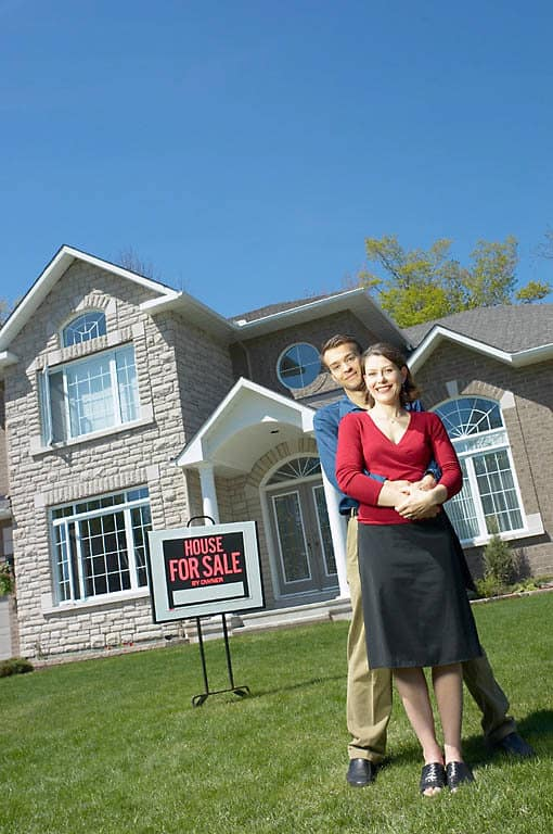 Smiling_young_couple_in_front_of_their_new_home_3.jpg
