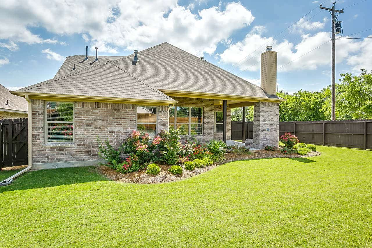 Single story custom built home with light brick, light colored roof and large patio with landscaping and green grass.