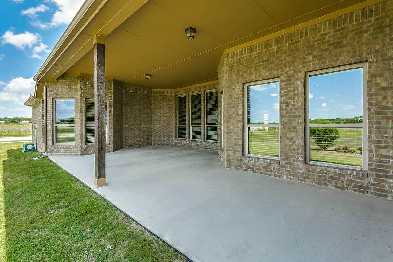 Large concrete patio in the backyard of a custom built home with large windows and brick siding.