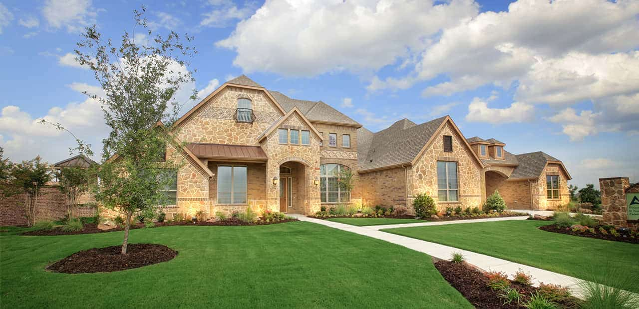 Large two story custom built home with large windows and light brown colored roofing.