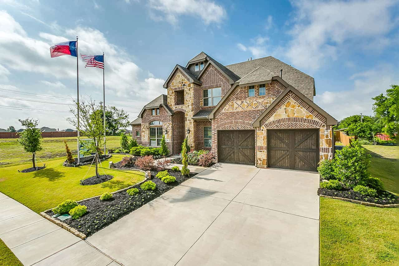 Two story custom built home with two car garage, two flags on large flag poles in the front yard and landscaping with trees and bushes.
