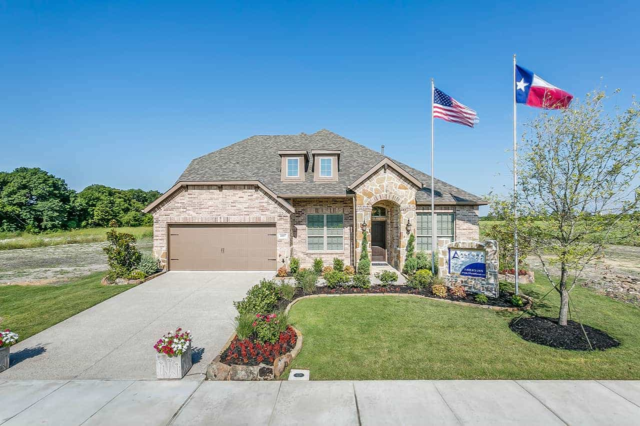 Custom built home with two car garage, lite colored brick, two flags on large flag poles in the front yard and landscaping with tree and bushes. (1)