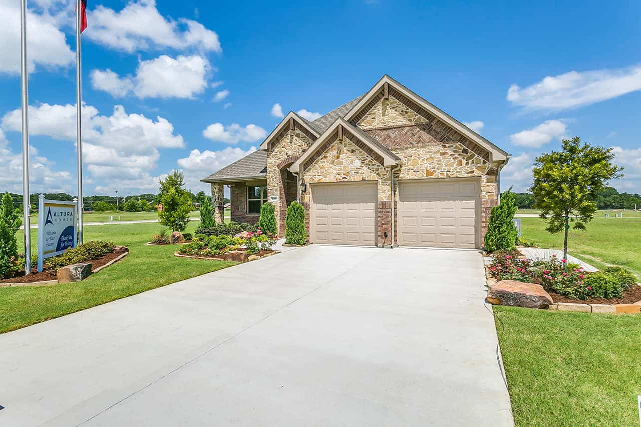 Ranch style custom built home with two car garage, stone exterior and landscaped front yard.