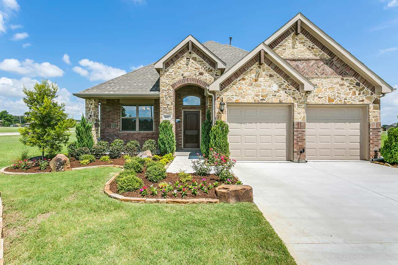 Ranch style custom built home with covered archway over front door, two car garage, stone exterior and landscaped front yard.