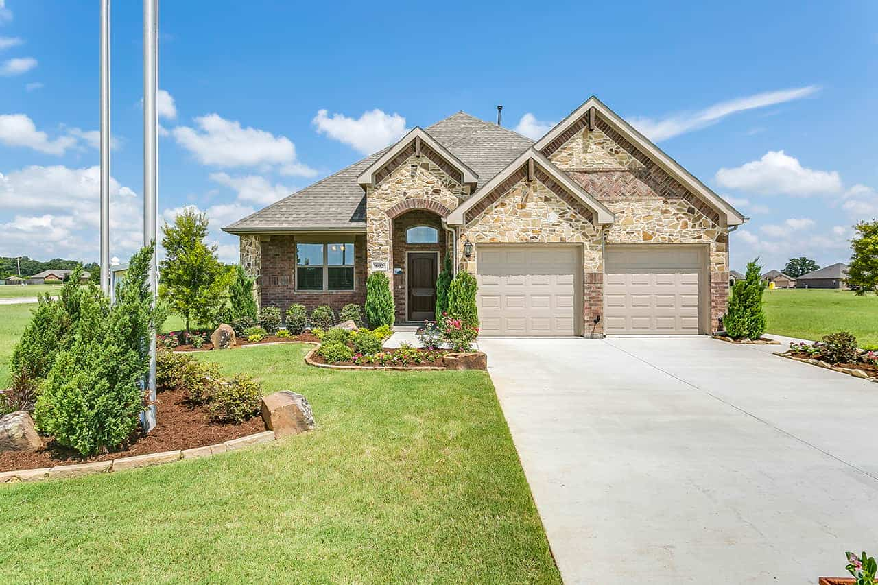 Ranch style custom built home with covered archway over front door, two car garage, stone exterior and landscaped front yard. (1)