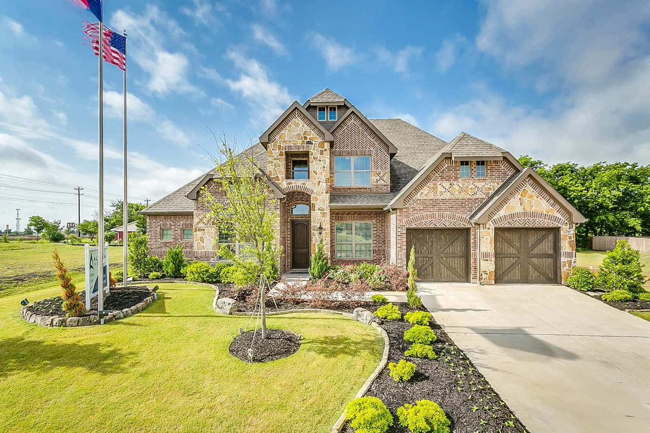 Two story custom built home with stone exterior, two car garage, large covered entry way over front door and a landscaped front yard.