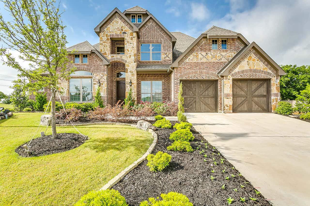 Two story custom built home with stone exterior, two car garage, large covered entry way over front door and a landscaped front yard. (1)