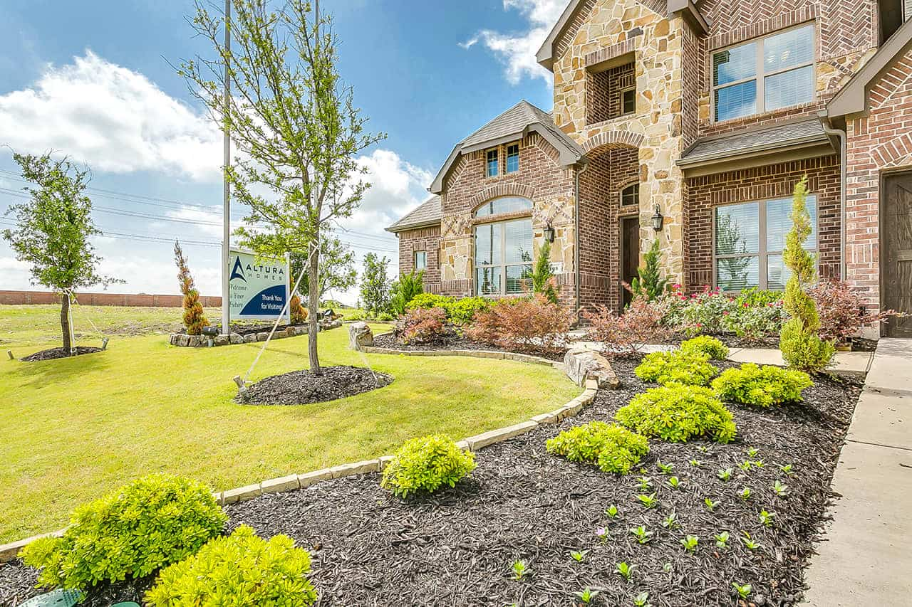 Two story custom built home with stone exterior, two car garage, large covered entry way over front door and a landscaped front yard. (2)